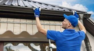 Worker installing a new gutter