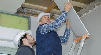 Two men repairing a roof leak in Stockton